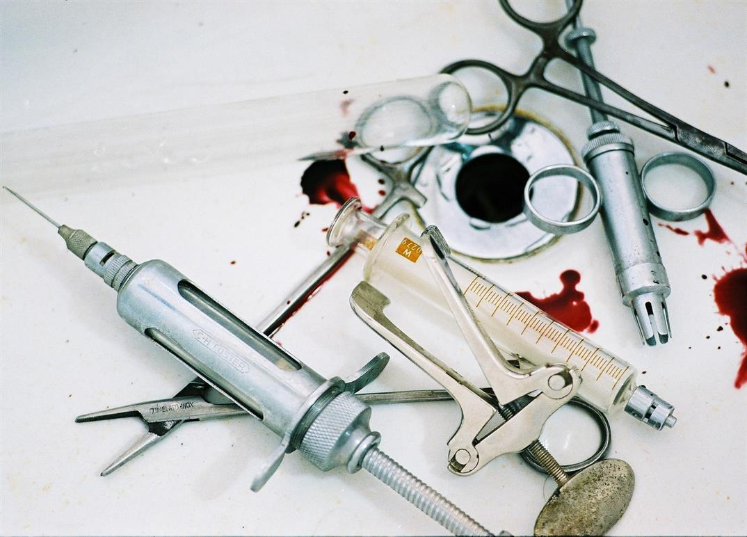 Surgical tools in a sink with drops of blood